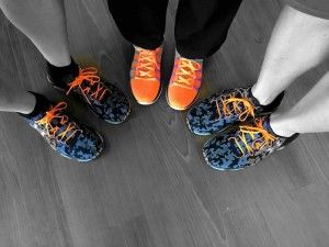 three pair of feet in a circle, multicolored tennis shoes